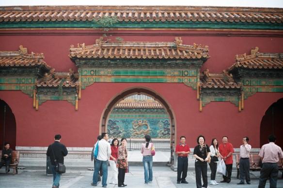 Група китайски туристи се усмихват на снимащата ги чужденка